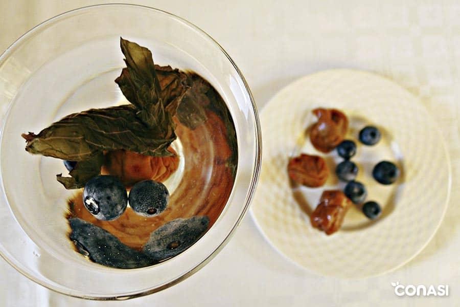 Infusión de umeboshi y arándanos en un vaso de cristal endulzado con hojas de stevia