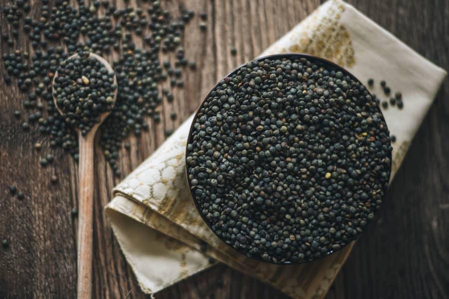 Lentejas negras en un bol y una cuchara con las legumbres.