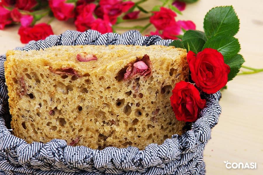 Trozo de pan con pétalos de rosa en una cesta