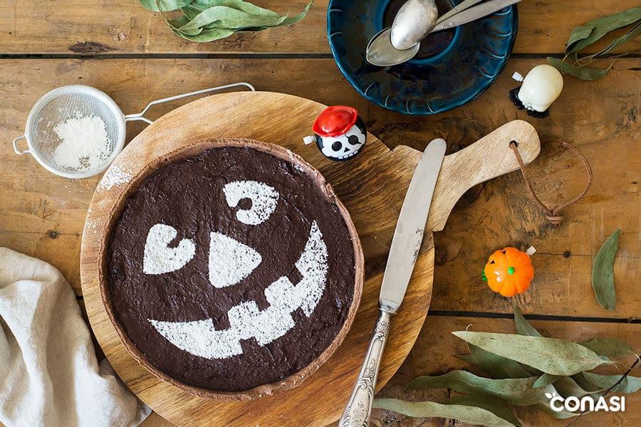 Tarta vegana de Halloween con una cara dibujada con harina de arroz encima de una mesa.