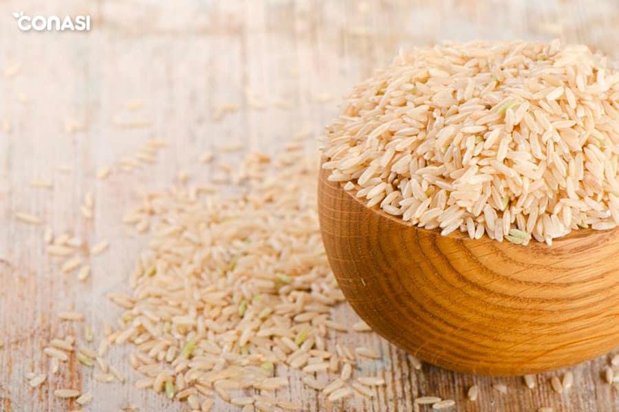 Cuenco de madera con arroz integral y algunos granos encima de la mesa - tipos de arroz integral