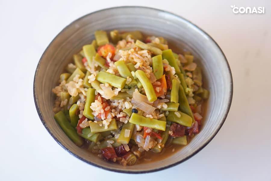 Vista de un cuenco con arroz caldoso con verduras y judías verdes.