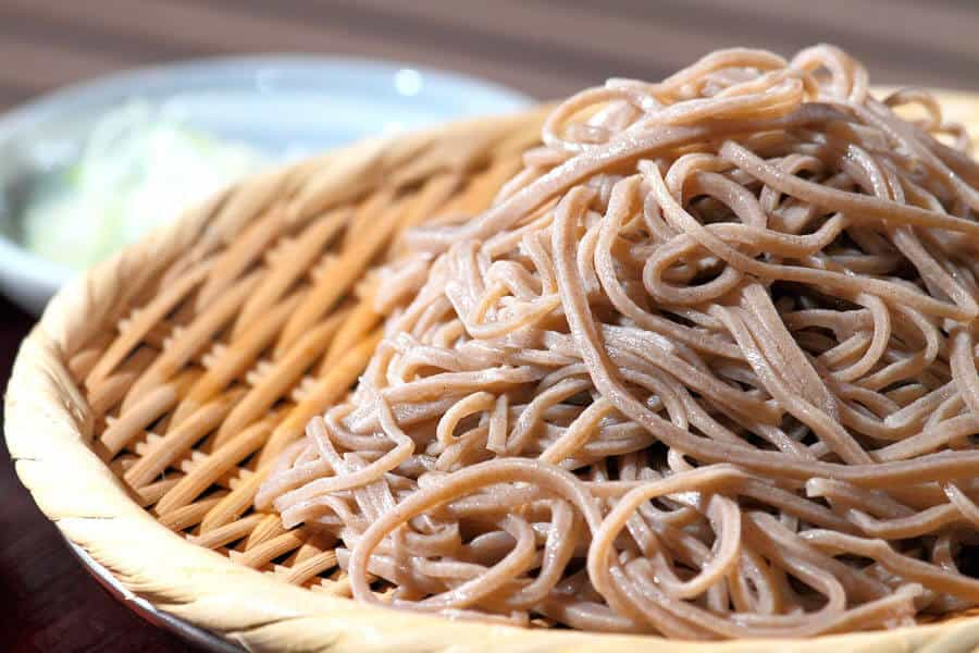 Fideos finos de trigo sarraceno sobre un plato de mimbre.
