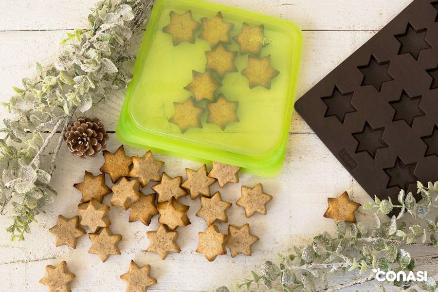 Galletas de tahini junto al molde de estrellas y una bolsa stasher.