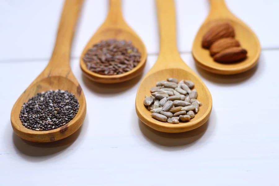 Cuatro cucharas de madera con diferentes semillas - Polifenoles y microbiota