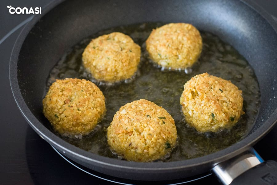 Croquetas vegetarianas redondas en una sartén skk con aceite de oliva.