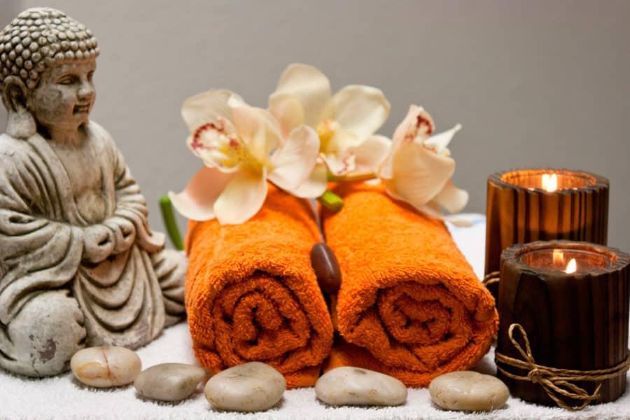 Budha, toallas, velas y flores para un masaje Ayurveda