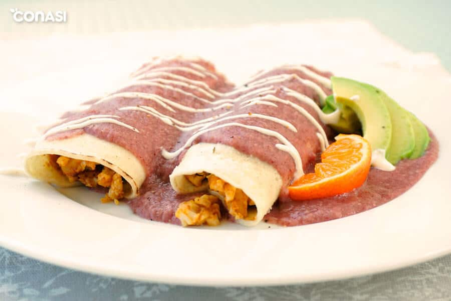Dos enchiladas con salsa y relleno de coliflor en un plato.