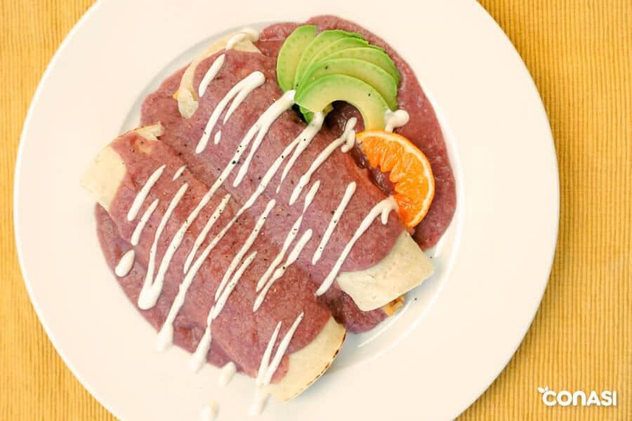 Dos enchiladas con salsa junto a aguacate laminado y un gajo de naranja.