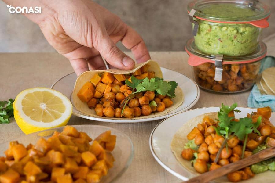 Una mano cogiendo tacos vegetarianos