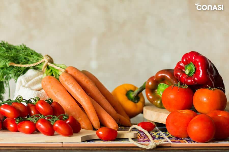 Cómo cocinar hortalizas - zanahorias, tomates y pimientos en una mesa