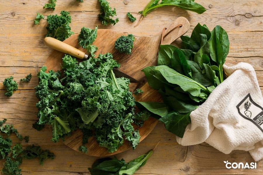 Col kale sobre una tabla y espinacas en la bolsa vejibag - hojas verdes