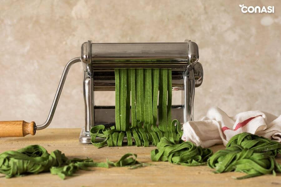 Pasta fresca de espinacas saliendo de la máquina para hacer pasta