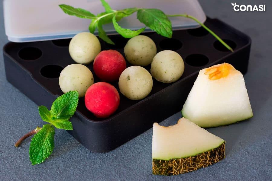 Cubitos de melón y sandía en la cubitera para el agua de jengibre