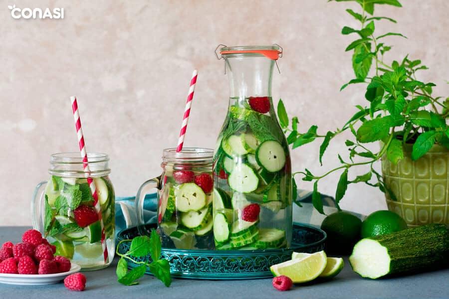 Agua de pepino con frambuesas, hierbabuena y lima en una jarra y botella