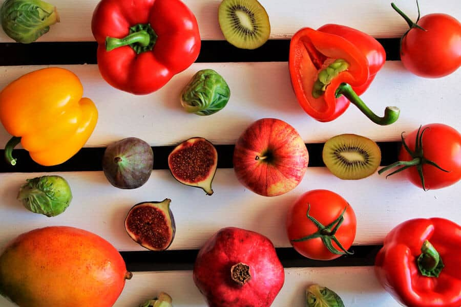 Frutas y pimientos sobre un fondo blanco - Salud cardiovascular y alimentación vegetal
