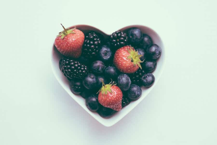 Fresas, moras y arándanos en un cuenco en forma de corazón - Cáncer y alimentación vegetariana