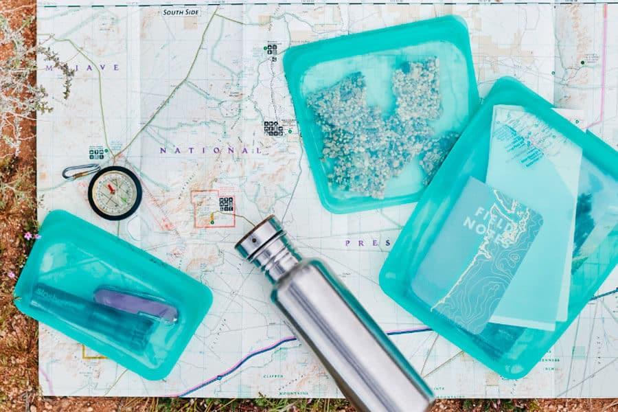 3 bolsas reutilizables Stasher con diferentes cosas sobre un mapa