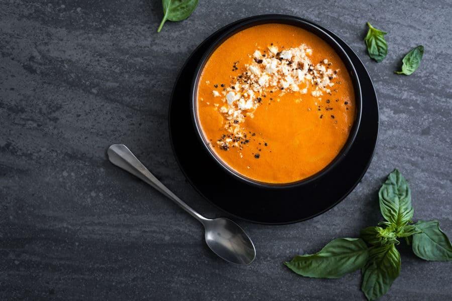 Sopa de pimientos asados con queso por encima en un bol negro junto a hojas de albahaca
