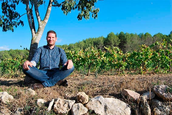 Damien Carbonnier sentado en un cultivo de árboles frutales