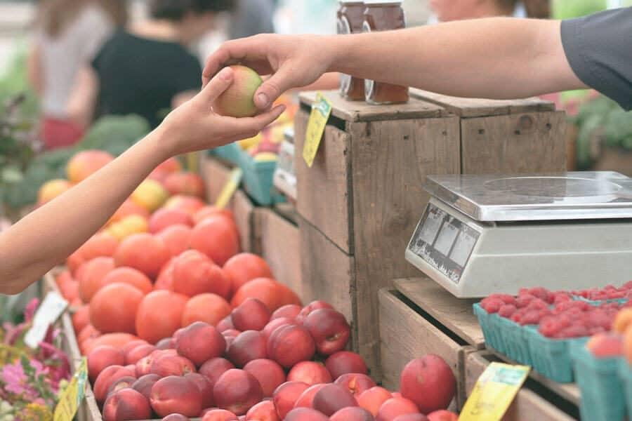 Frutero dando una manzana a otra persona - Propósitos sostenibles Año nuevo