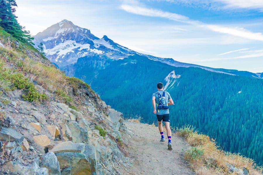 Persona haciendo trail y al fondo un paisaje de montaña - Propósitos sostenibles Año nuevo