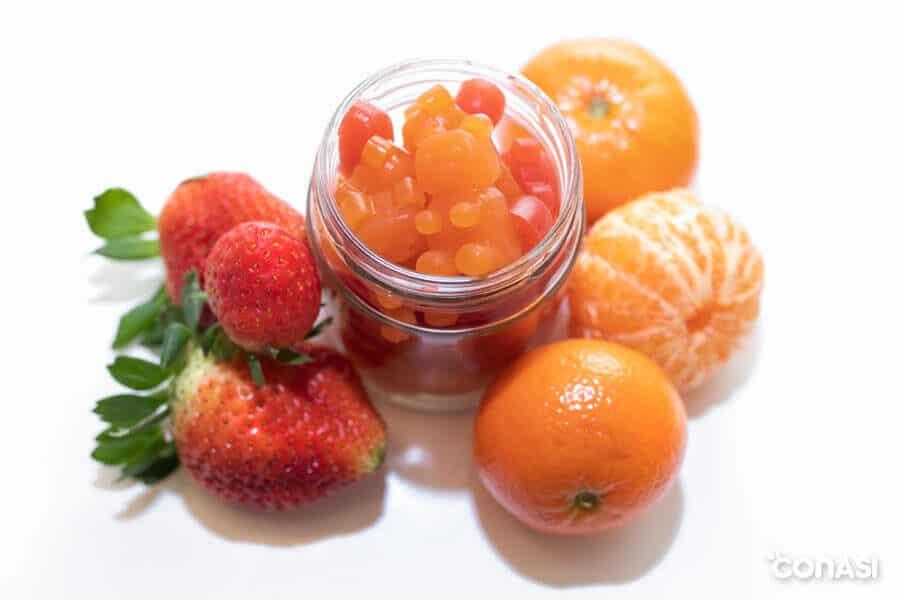Gominolas caseras en un taro de cristal junto a mandarinas y fresas