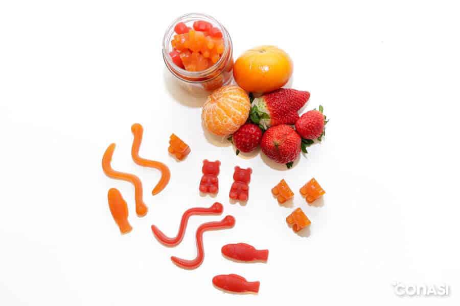 Gominolas de frutas en un taro de cristal junto a mandarinas y fresas