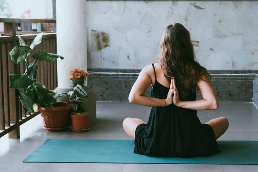 Mujer haciendo yoga en el balcón - Fortalecer el sistema inmune