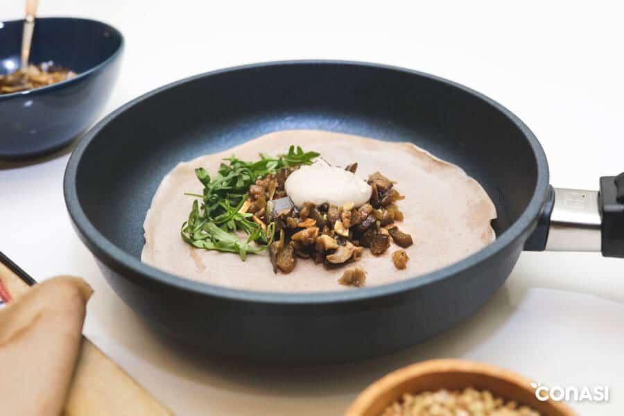 Galette bretona en la sartén con los ingredientes del relleno