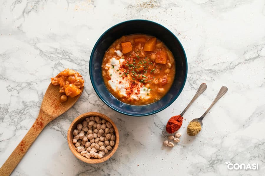 Potaje de garbanzos con arroz en un bol junto a algunos de sus ingredientes