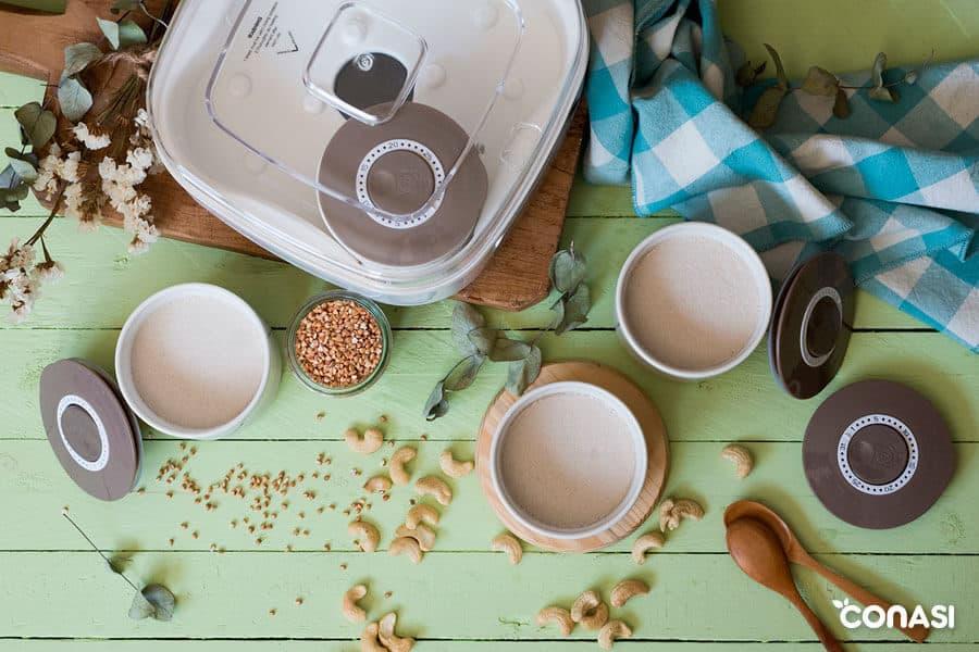 Yogur vegano de anacardos y sarraceno en sus recipientes junto a la yogurtera