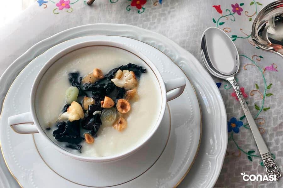 Cuenco de sopa con crema de coliflor y trompetas de la muerte arriba